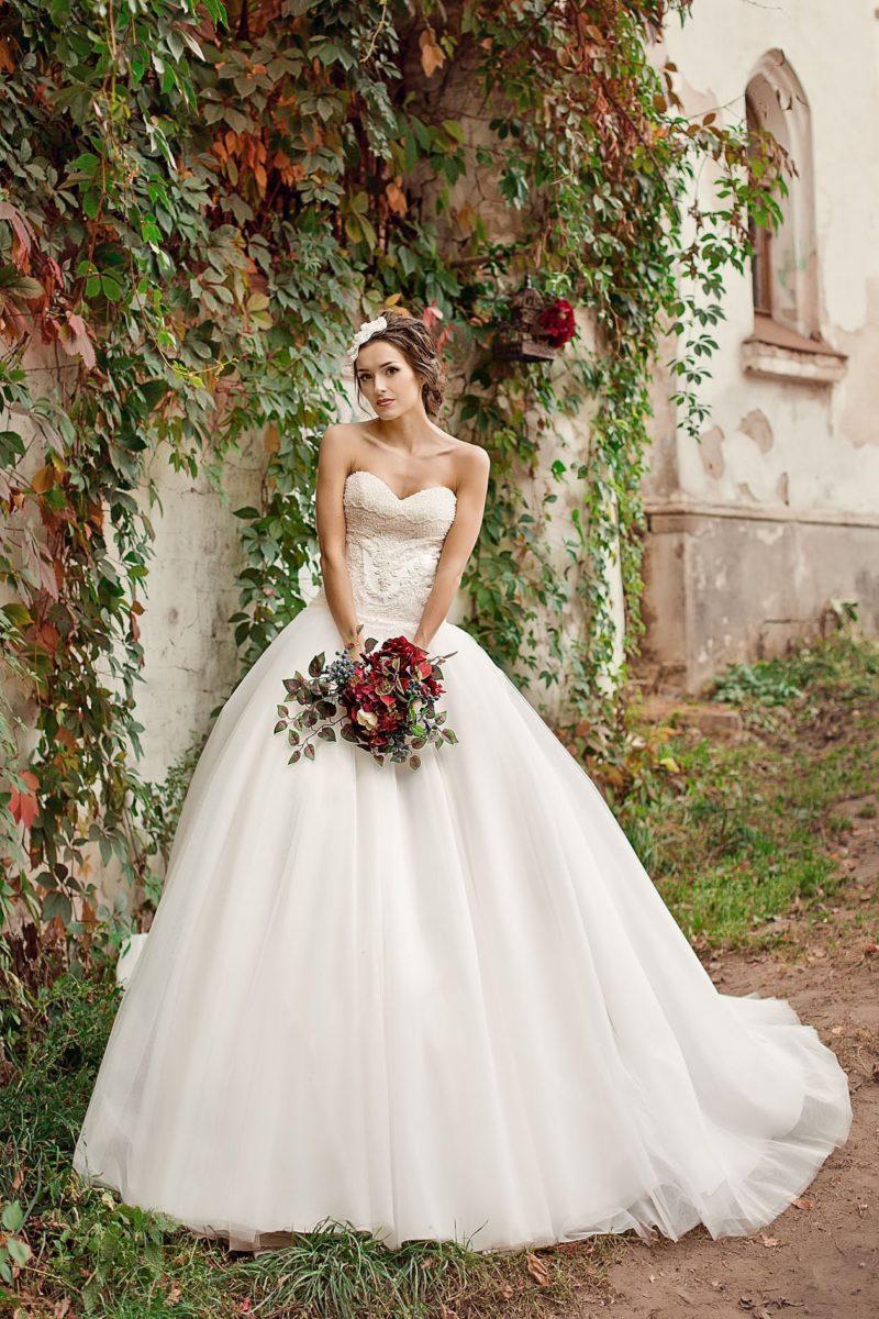 Открытое свадебное платье с пышной юбкой со шлейфом и нежным кружевным корсетом.