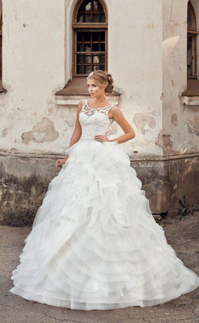 Пышное свадебное платье с многоярусным декором подола и изящным кружевным верхом.