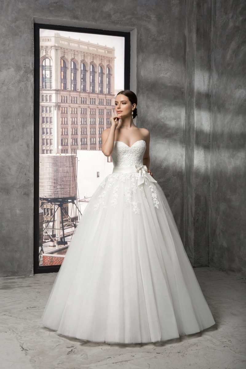 Открытое свадебное платье с роскошным кружевным корсетом, поясом на талии и пышным низом.
