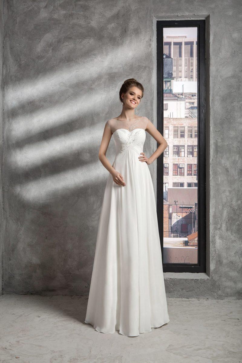 Нежное свадебное платье прямого кроя с верхом, оформленным тонкой тканью с вышивкой.