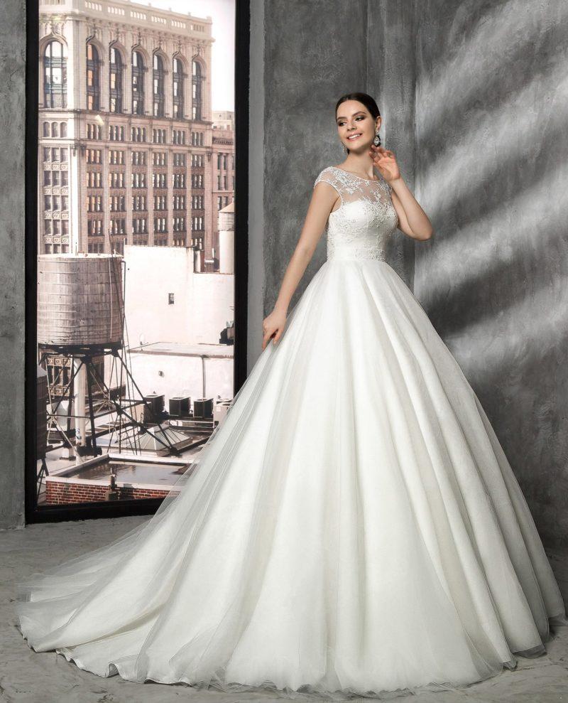 Пышное свадебное платье с полупрозрачной тканью верха, украшенной аппликациями.