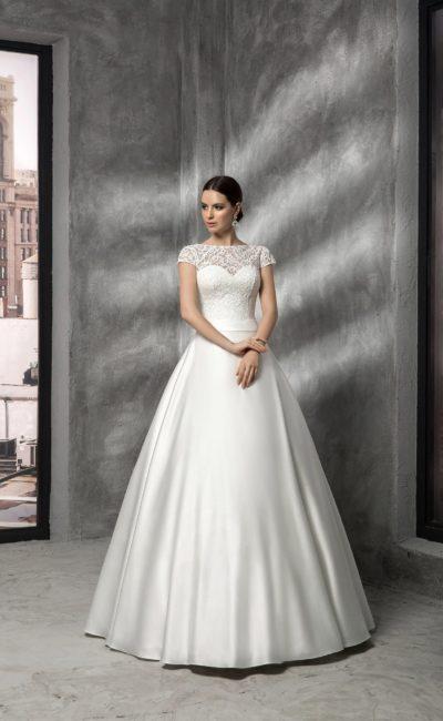 Пышное свадебное платье из атласа, дополненное кружевными рукавами и округлым вырезом.