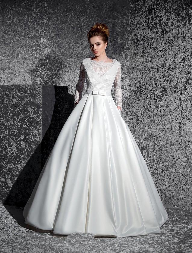 Закрытое свадебное платье с пышной юбкой со скрытыми карманами и изящным кружевным верхом.