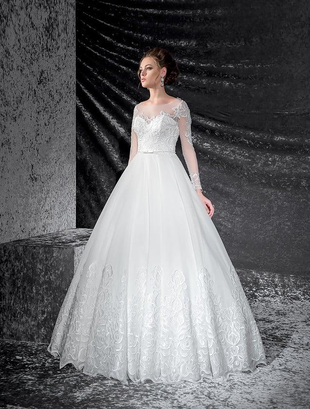Пышное свадебное платье с полупрозрачными рукавами и кружевным декором низа юбки.