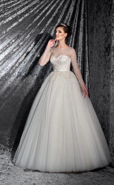 Свадебное платье с многослойной юбкой и атласным корсетом, оформленным тонкой тканью.