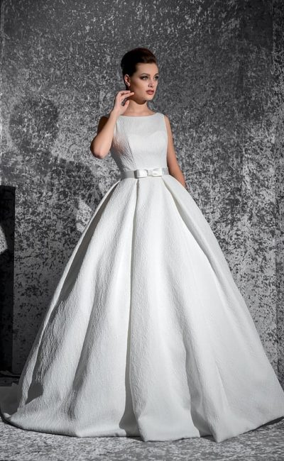 Изысканное свадебное платье с вырезом бато и атласным поясом над пышной юбкой с карманами.
