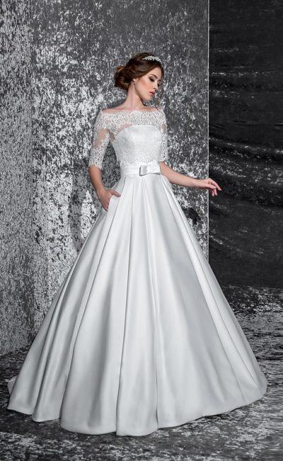 Атласное свадебное платье с широким поясом, украшенным бантом, и кружевной отделкой верха.