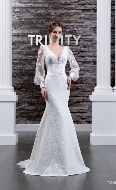 Свадебное платье «русалка» с глубоким вырезом, широкими рукавами и кружевным декором юбки.