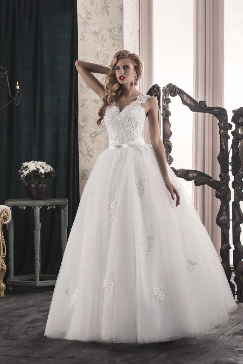 Пышное свадебное платье с широкими кружевными бретелями и атласным поясом.