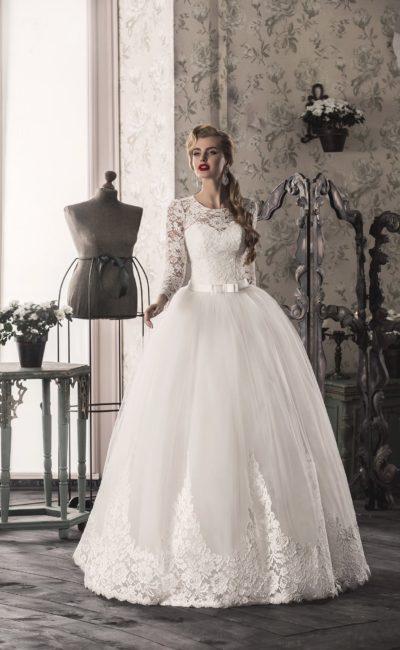Закрытое свадебное платье с округлым вырезом и многослойной юбкой, дополненное атласным поясом.