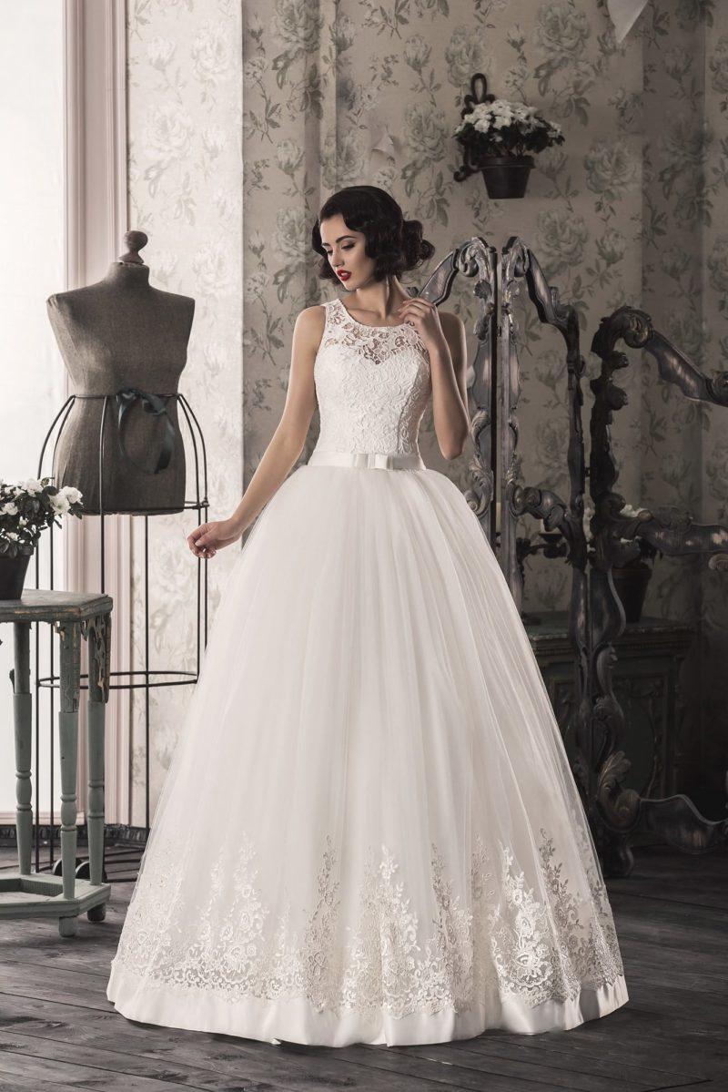 Торжественное свадебное платье с округлым вырезом и кружевной отделкой низа подола.