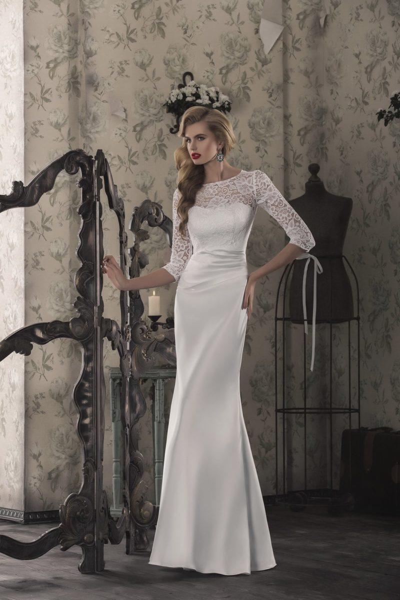 Прямое свадебное платье из атласа с закрытым кружевным верхом и облегающими рукавами.