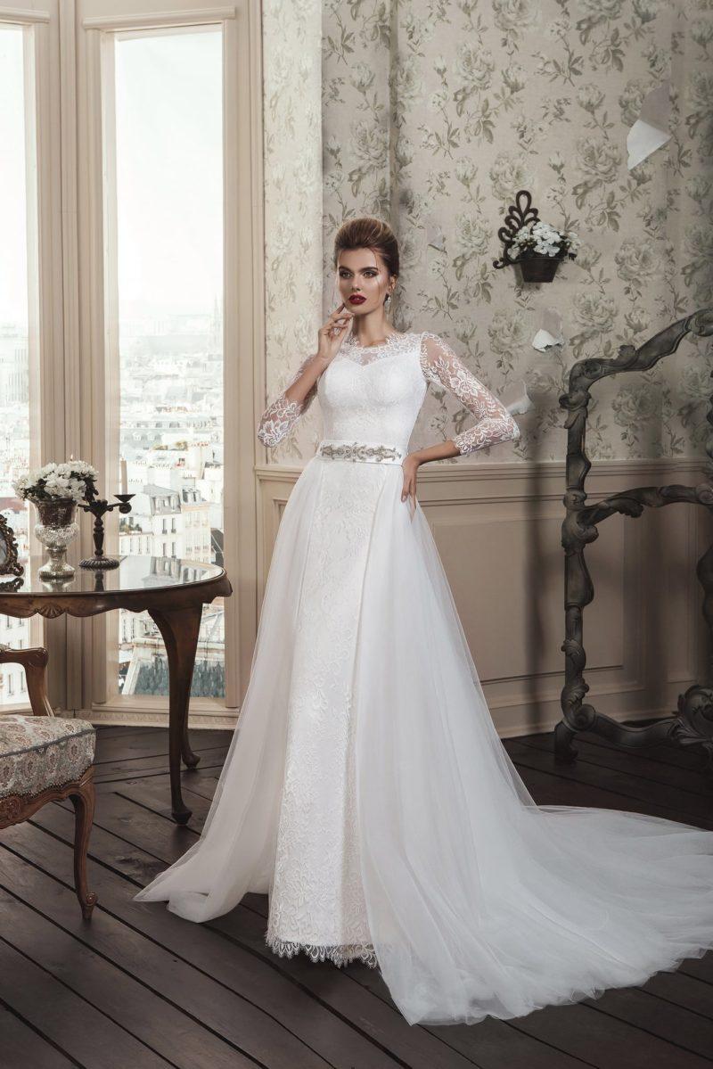 Драматичное свадебное платье прямого кроя с длинным кружевным рукавом и верхней юбкой.