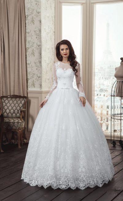 Закрытое свадебное платье с пышной кружевной юбкой и длинными полупрозрачными рукавами.
