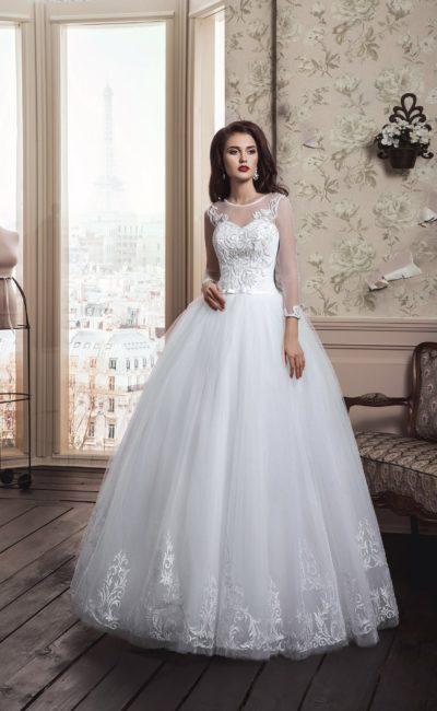 Закрытое свадебное платье пышного кроя с прозрачными рукавами и аппликациями на юбке.
