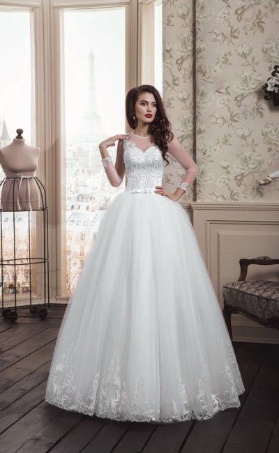 Элегантное свадебное платье с пышной юбкой и стильными прозрачными рукавами.