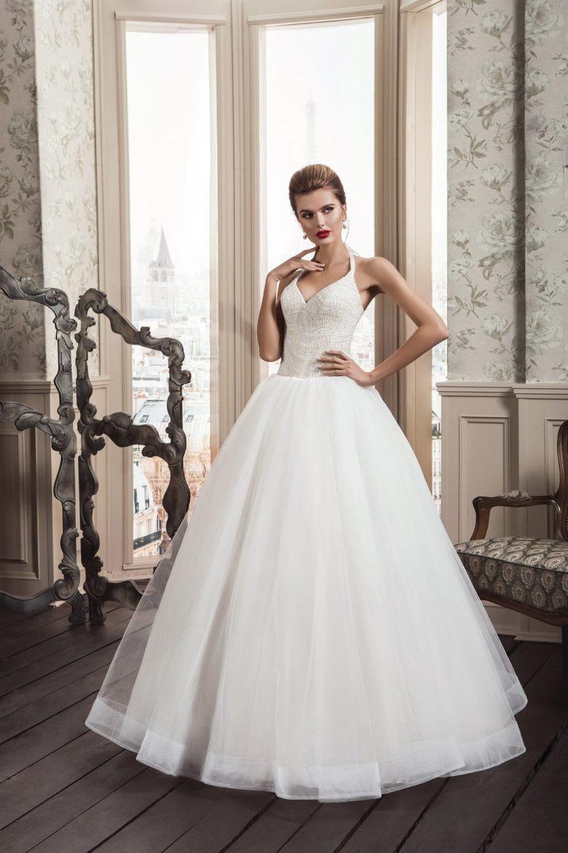 Лаконичное свадебное платье пышного кроя с изящной юбкой и соблазнительным верхом.