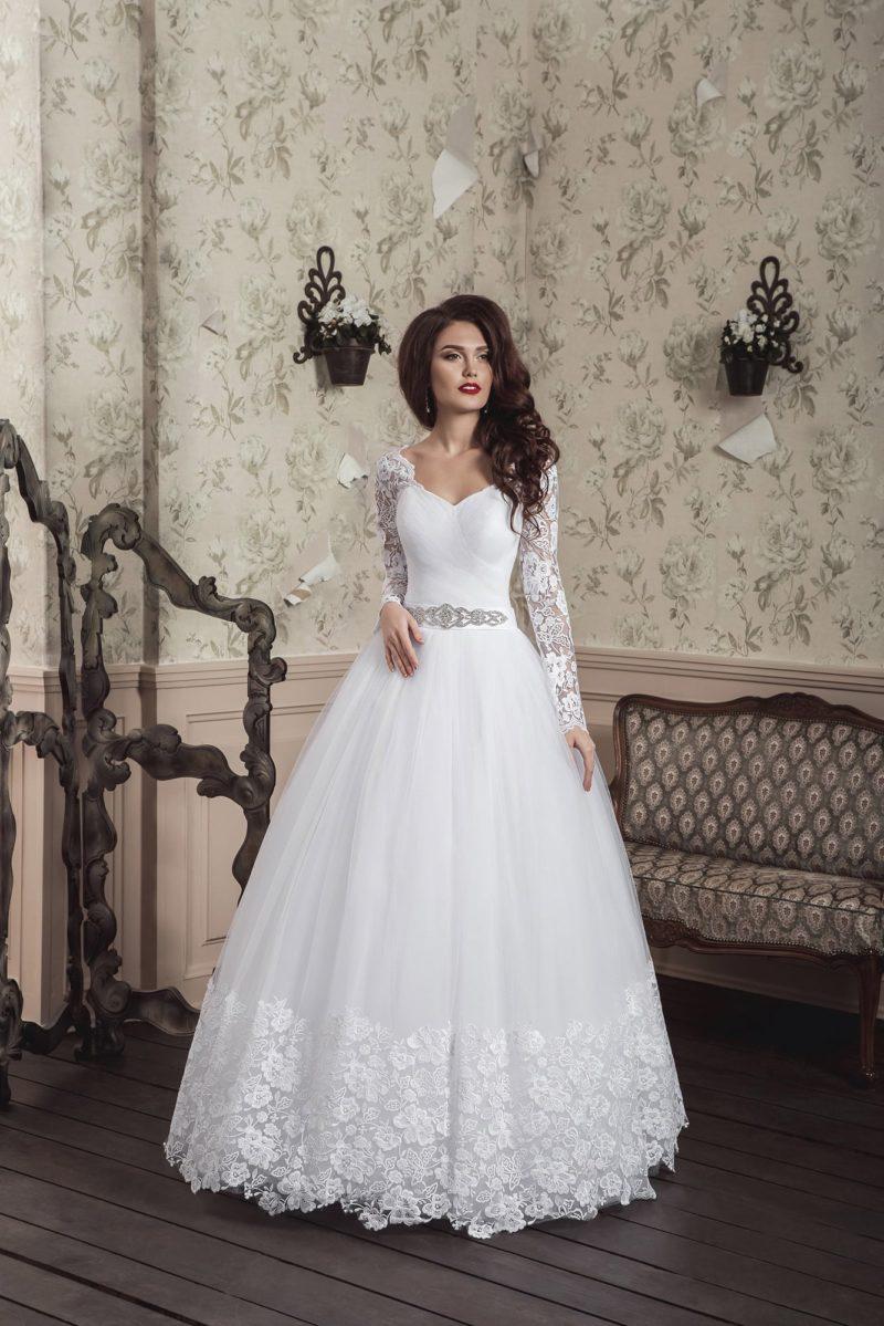 Пышное свадебное платье с V-образным вырезом и многослойной юбкой с кружевным декором.