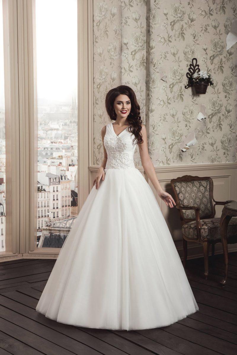 Изысканное свадебное платье с V-образным вырезом и кружевной отделкой верха.