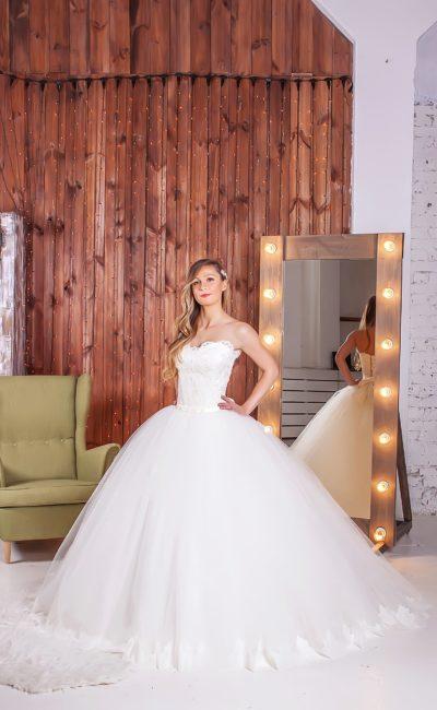 Свадебное платье с невероятно пышным силуэтом и открытым лифом, украшенным кружевом.
