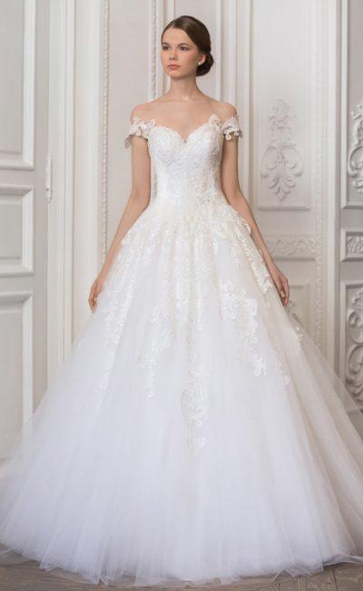 Романтичное свадебное платье с бретелями на предплечьях и кружевными аппликациями на юбке.