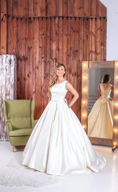 Впечатляющее свадебное платье с округлым вырезом, пышной юбкой и декольте на спинке.