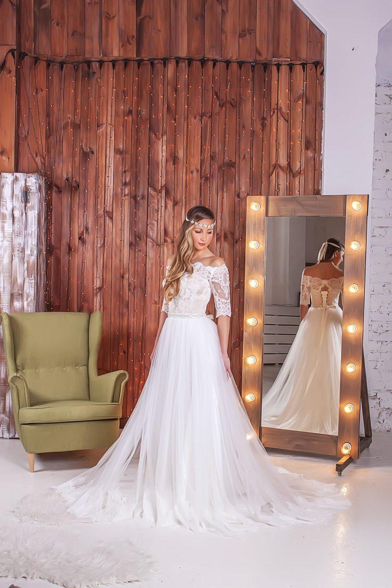 Нежное свадебное платье с полупрозрачным верхом юбки и кружевными рукавами до локтя.