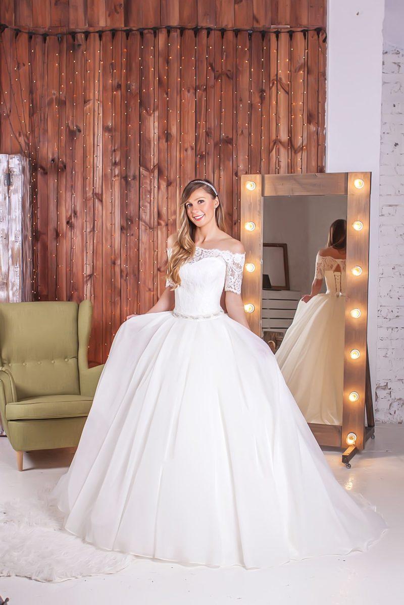 Роскошное свадебное платье пышного кроя с фигурным вырезом и стильными короткими рукавами.