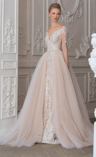 Кремовое свадебное платье с пышной верхней юбкой и кружевным декором по всей длине.