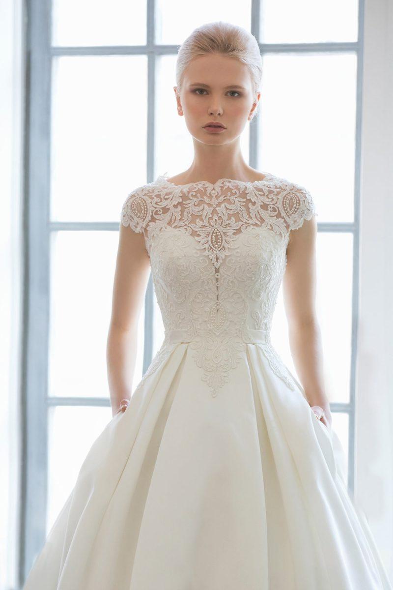 Скромное свадебное платье с кружевной отделкой лифа и атласной юбкой со скрытыми карманами.