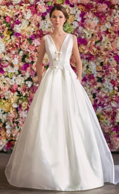 Атласное свадебное платье с пышной юбкой и глубоким V-образным декольте с бантами.