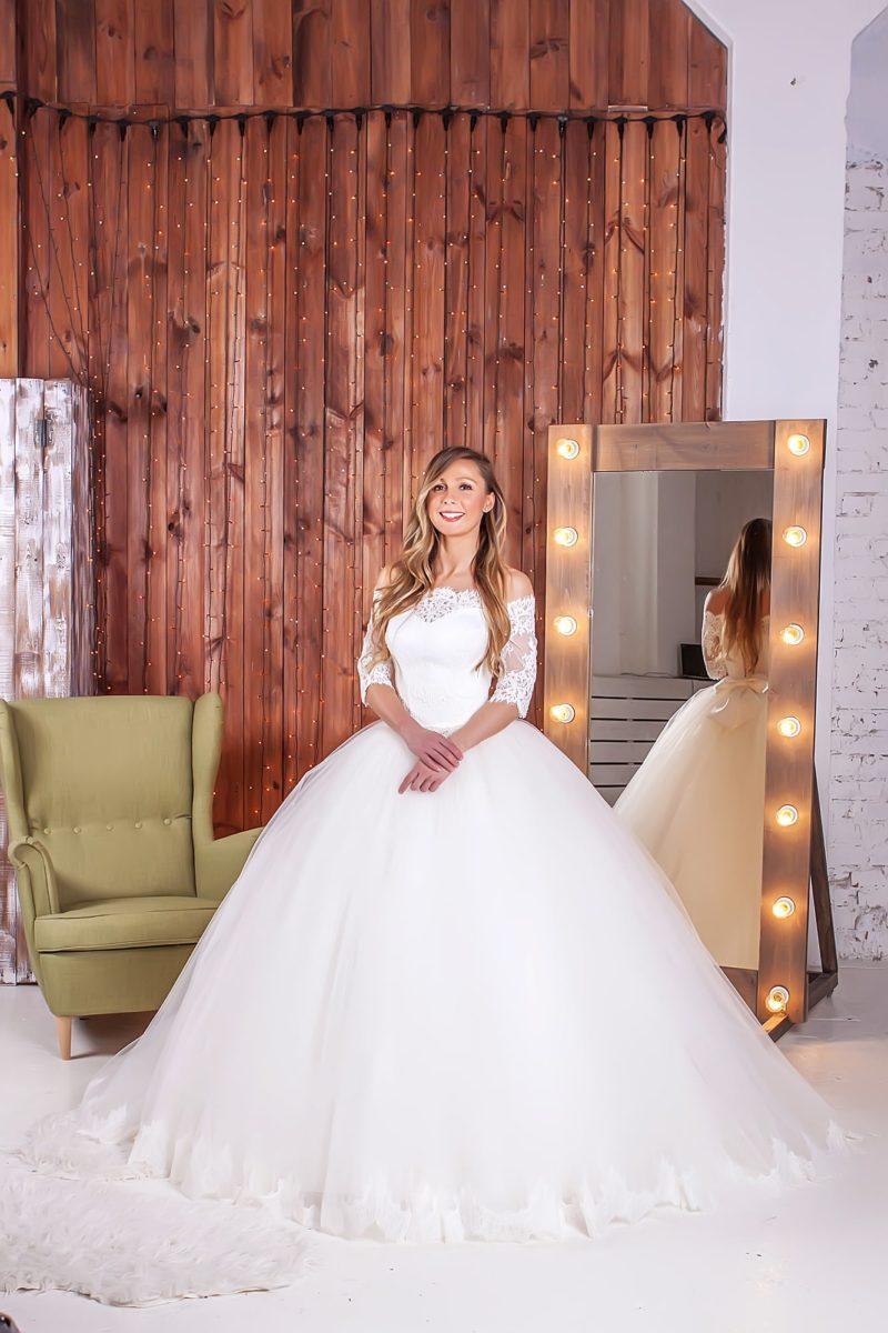 Торжественное свадебное платье с объемным подолом и портретным декольте, украшенным кружевом.