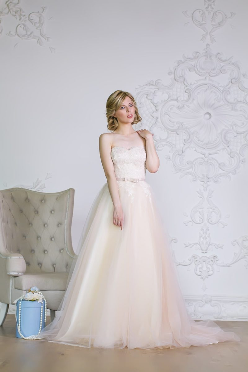 Кремовое свадебное платье в лаконичном стиле, с кружевным корсетом и узким поясом на талии.