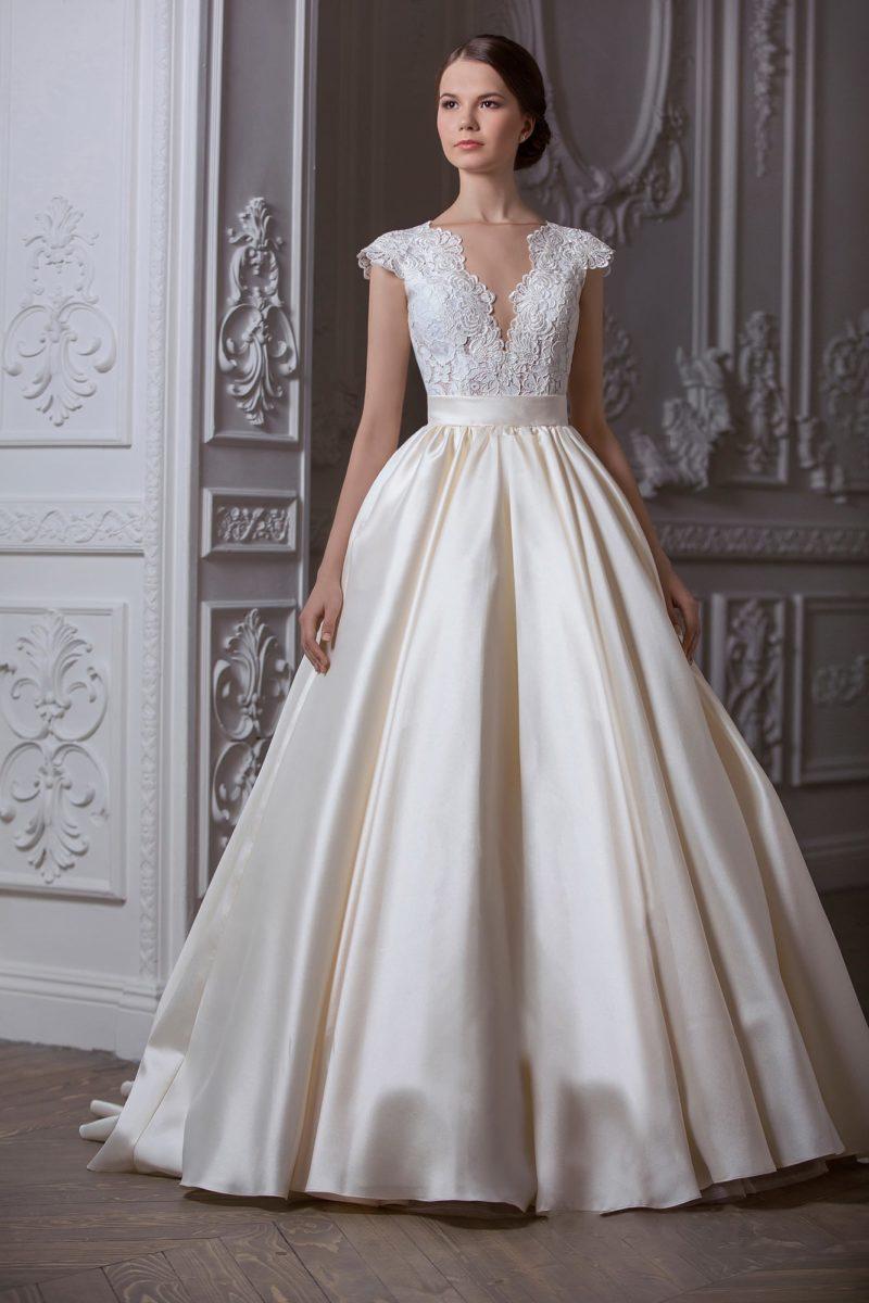 Великолепное свадебное платье с глубоким V-образным вырезом и пышной атласной юбкой.