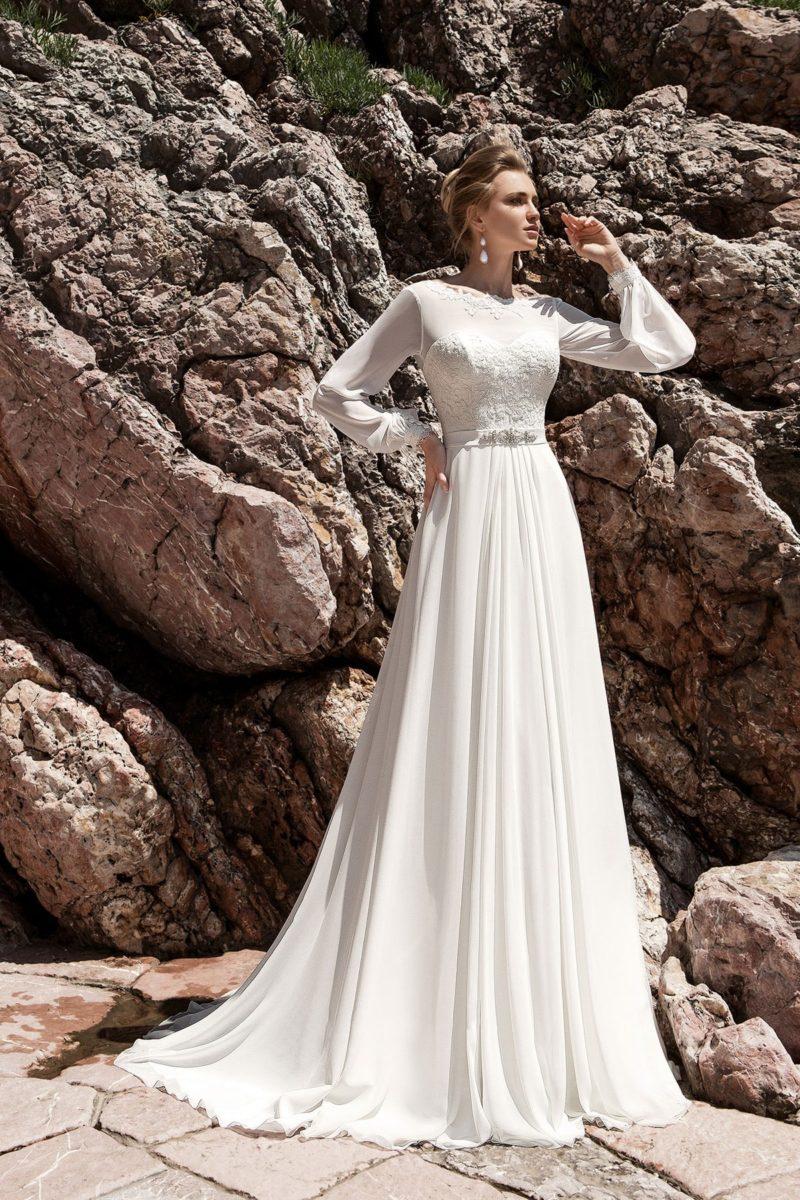 Свадебное платье с элегантной юбкой, украшенной складками ткани, и широкими рукавами.