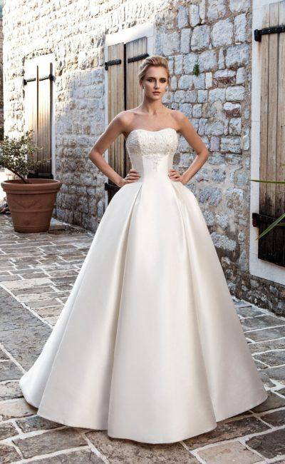 Атласное свадебное платье с открытым лифом и пышной юбкой с фижмами по бокам.