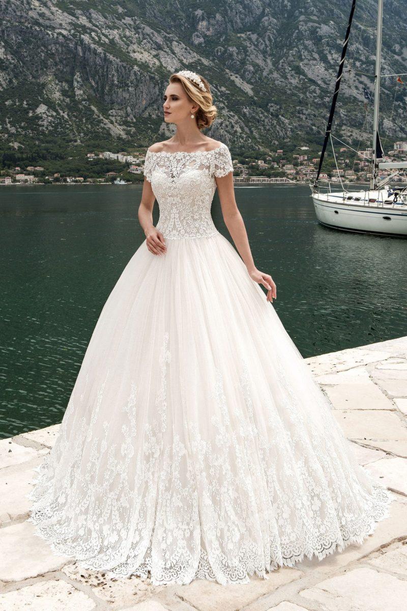 Свадебное платье с элегантным портретным декольте, коротким рукавом и многослойным подолом.