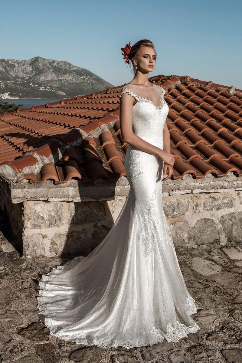 Атласное свадебное платье с полупрозрачной вставкой над лифом и изящным шлейфом сзади.