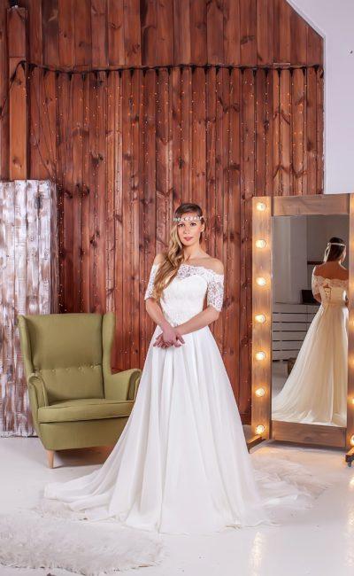 Женственное свадебное платье с портретным декольте, дополненным коротким рукавом, и юбкой со шлейфом.