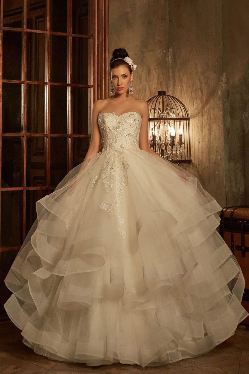 Пышное свадебное платье с многуровневой юбкой и открытым корсетом, украшенным аппликациями.
