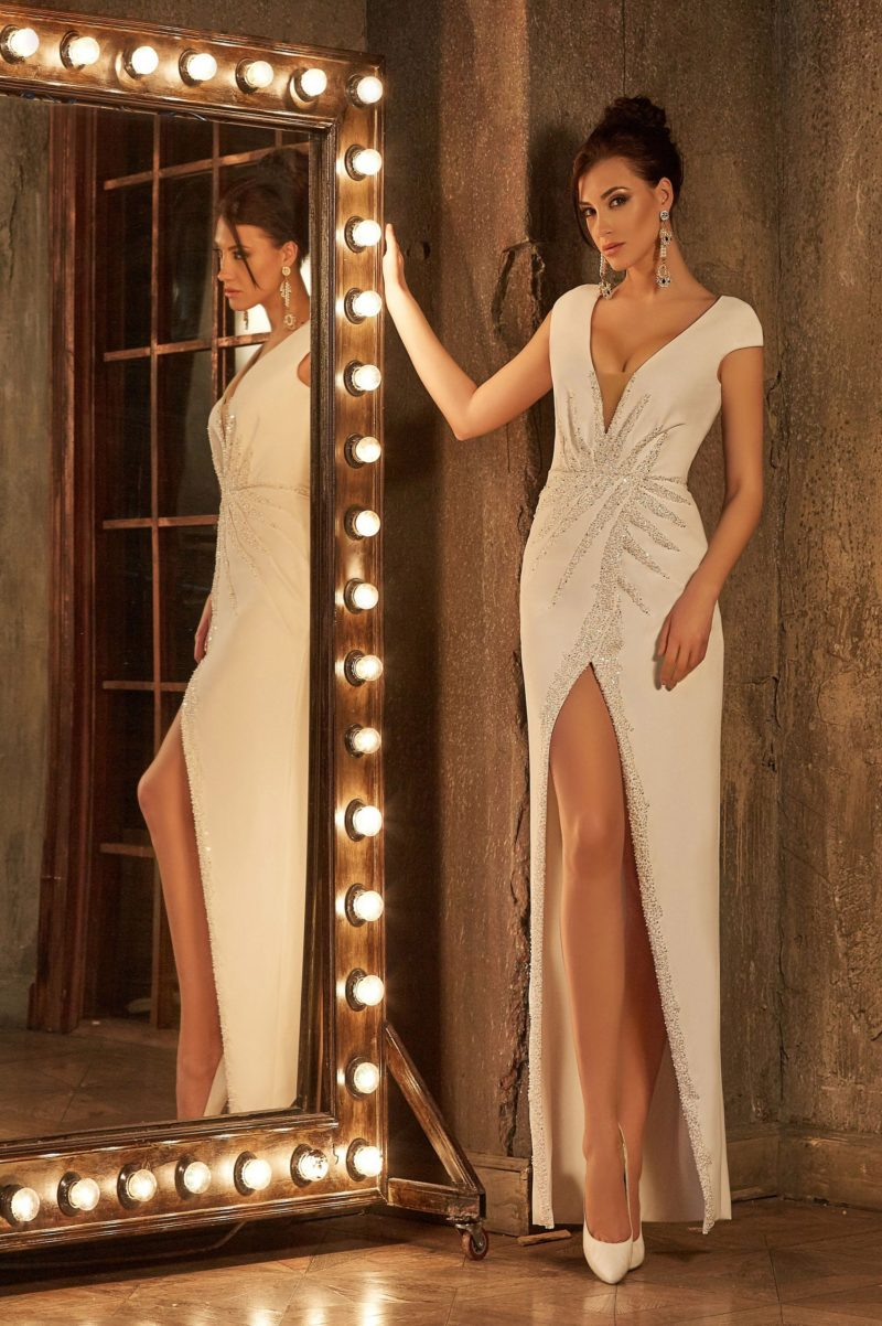 Прямое свадебное платье с соблазнительными разрезами, обрамленными бисерной вышивкой.