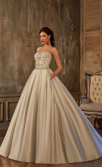 Свадебное платье с расшитым корсетом и пышной атласной юбкой со скрытыми карманами.