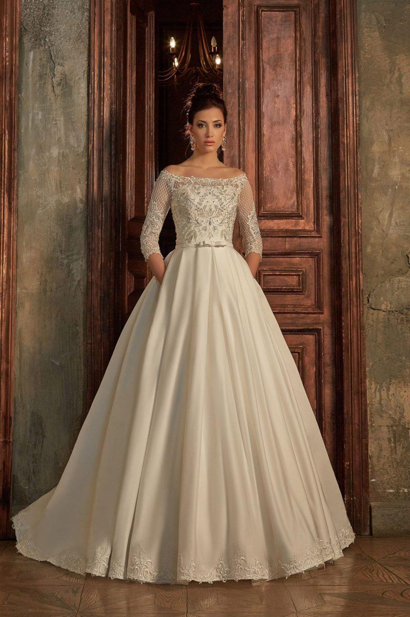Пышное свадебное платье с портретным декольте, кружевным рукавом и декором по низу подола.