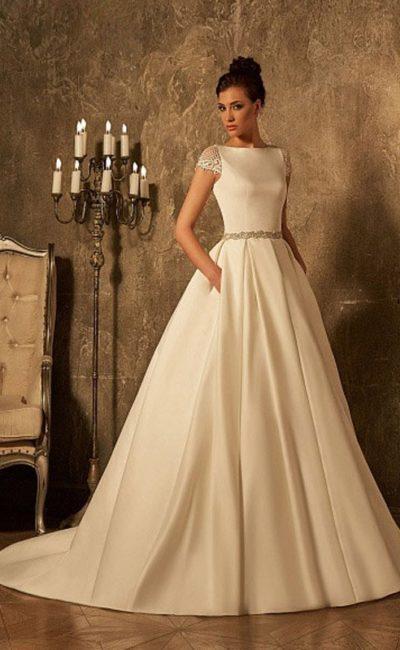 Атласное свадебное платье с округлым вырезом под горло и короткими кружевными рукавами.