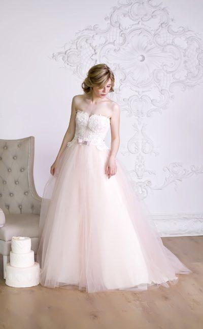 Свадебное платье с нежной розовой юбкой из множества слоев ткани и открытым верхом.