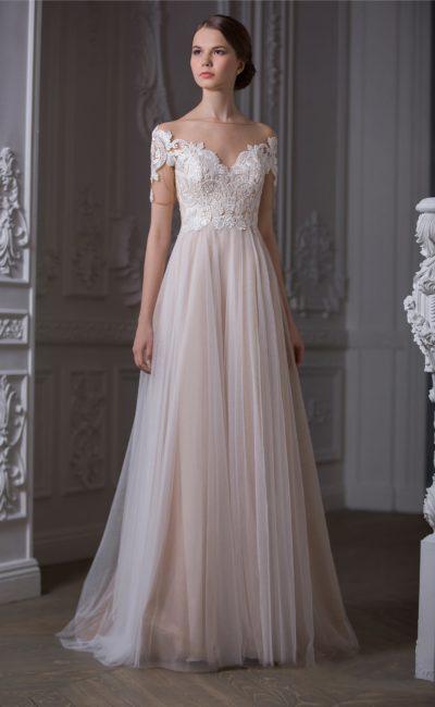 Свадебное платье с бежевой подкладкой многослойной юбки и кружевной отделкой верха.