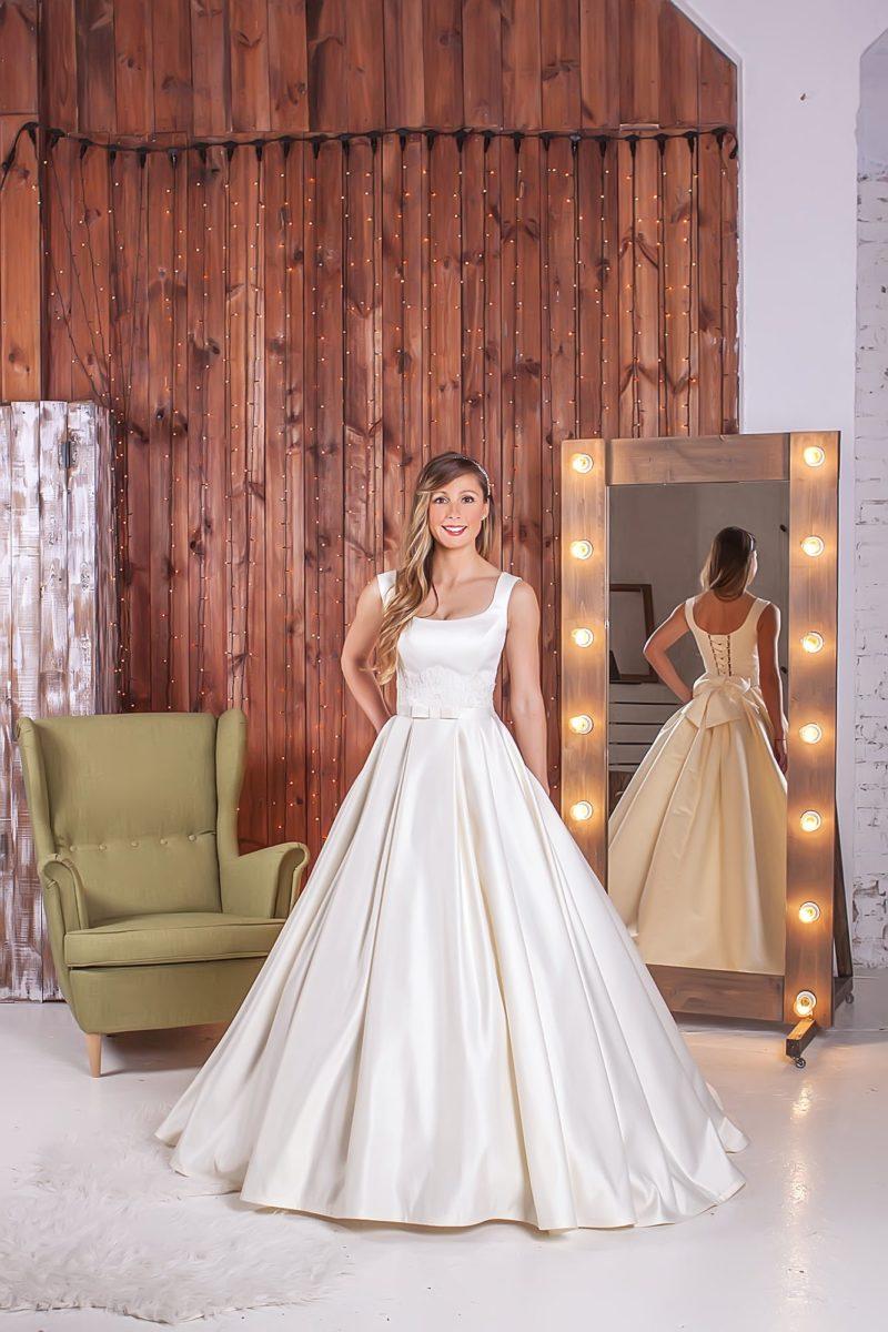 Атласное свадебное платье с округлым декольте и романтичным объемным бантом, украшающим спину.