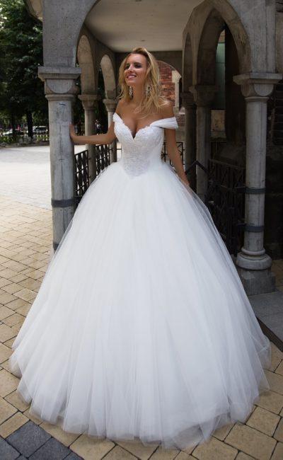 Бальное свадебное платье с бретелями на предплечьях и многослойной юбкой в лаконичном стиле.