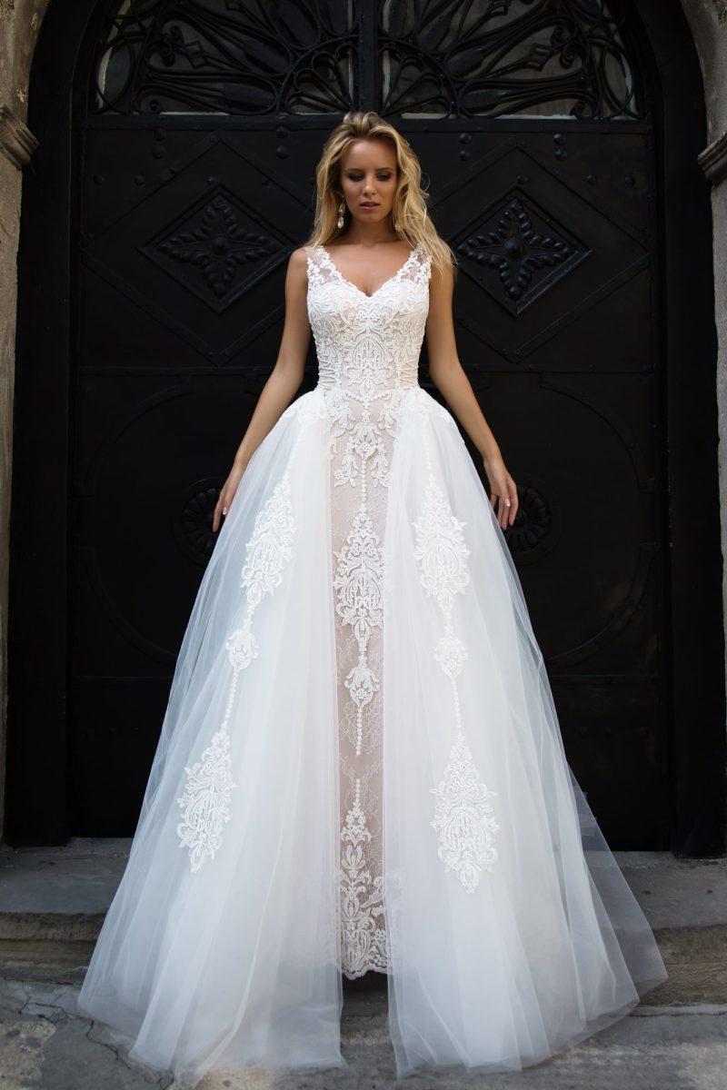 Пышное свадебное платье с V-образным декольте и бежевой подкладкой под белым кружевом.