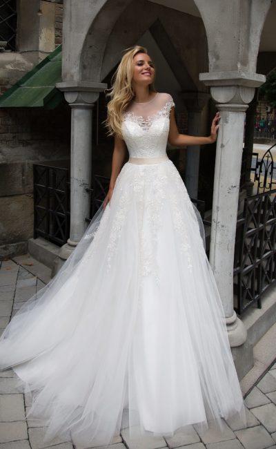Свадебное платье А-кроя с тонкой вставкой над лифом и многослойной объемной юбкой.